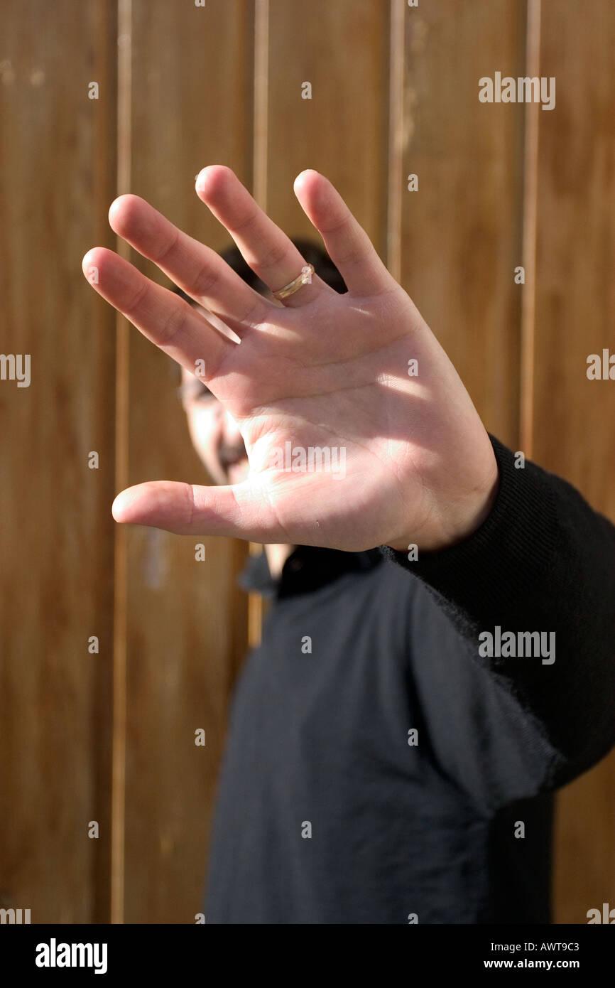 L uomo lo stiramento del suo braccio faccia Nascondi Immagini Stock