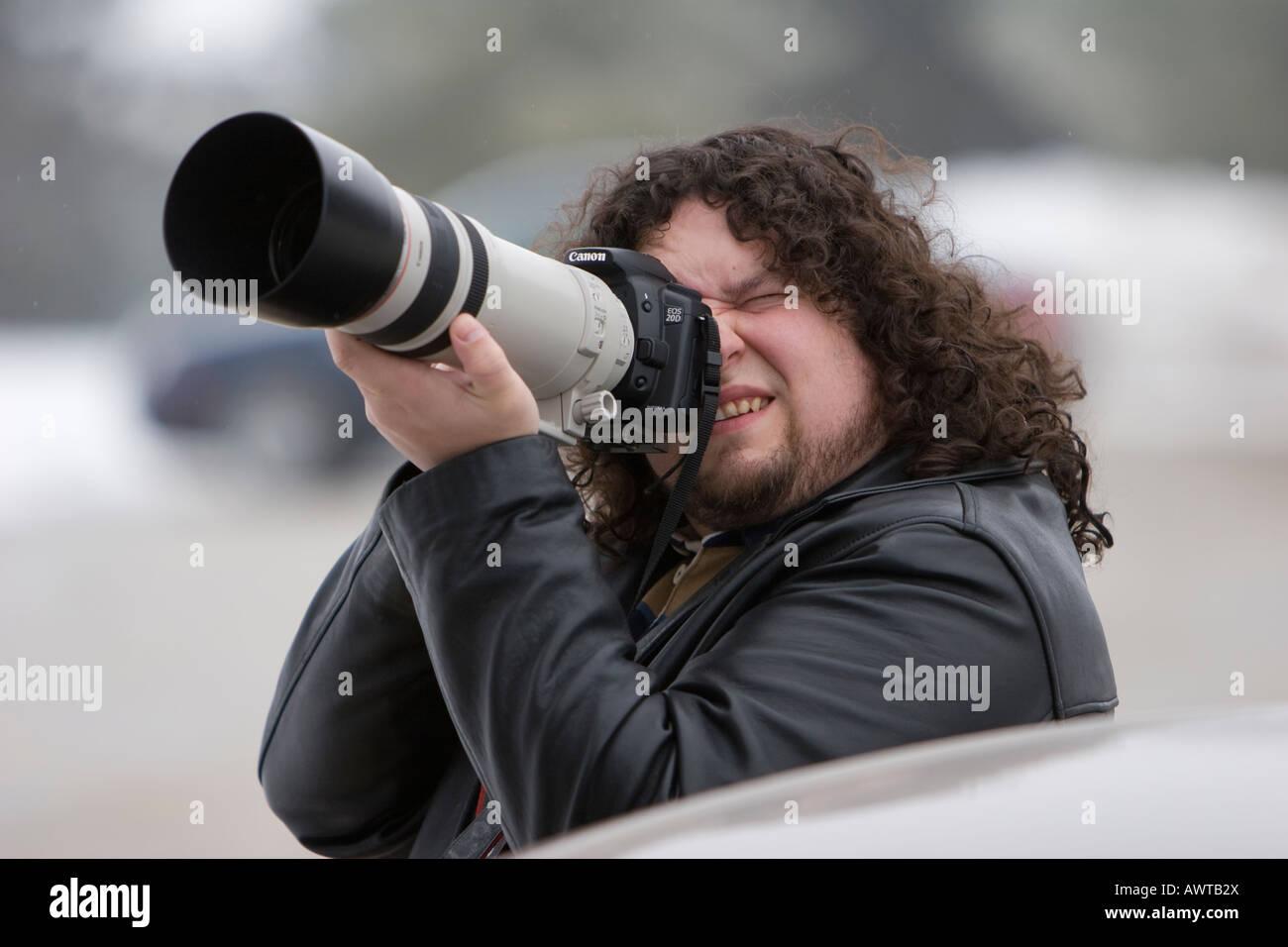 Un uomo con un lungo un teleobiettivo Canon 100 400 Immagini Stock