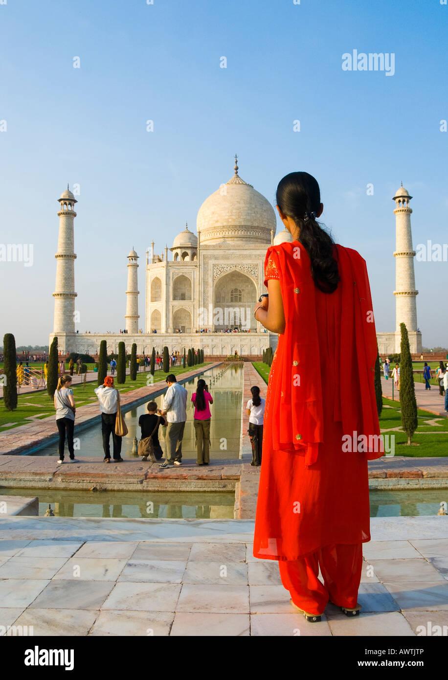 Una donna in un sari rosso davanti al Taj Mahal in Agra India Immagini Stock
