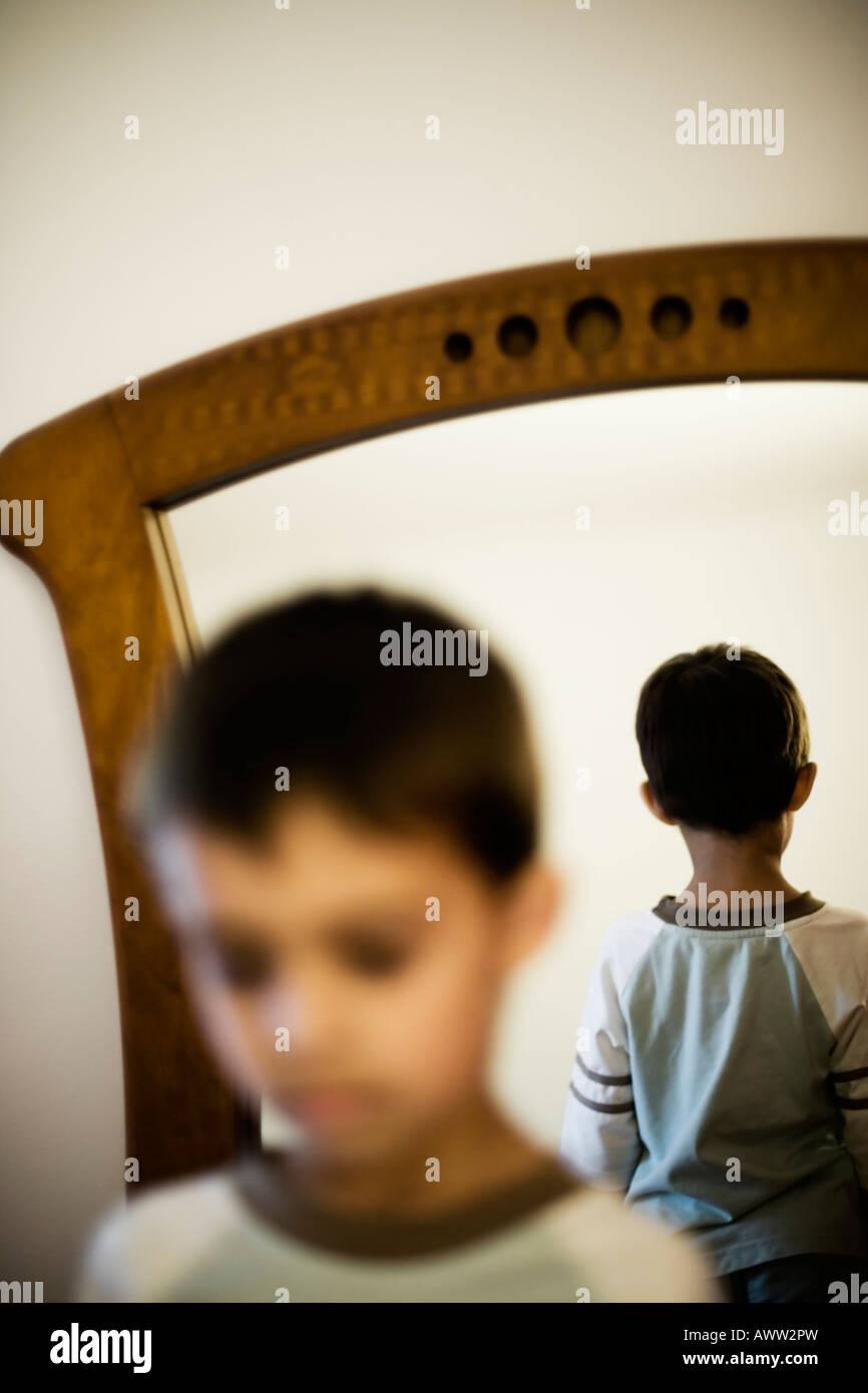 Faccia con la parte posteriore della testa riflessa in uno specchio Immagini Stock