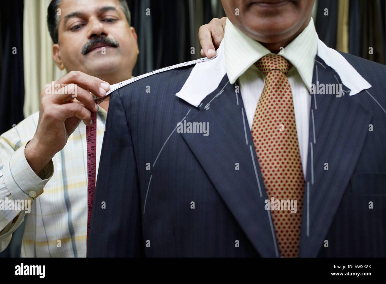 Adattare la misura uomo d affari con nastro di misurazione, close up Immagini Stock