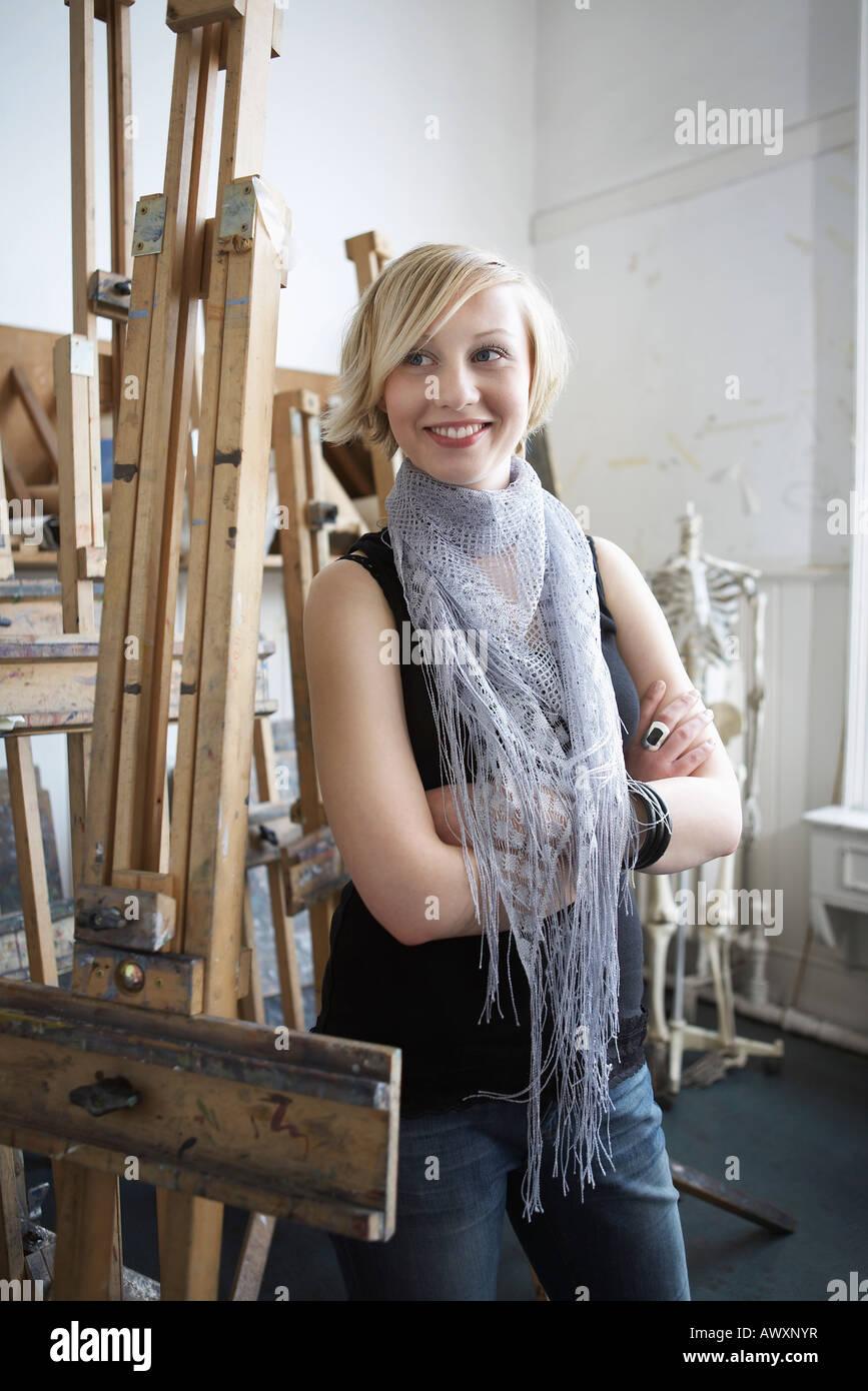 Studentessa piedi tra i cavalletti in art college Immagini Stock