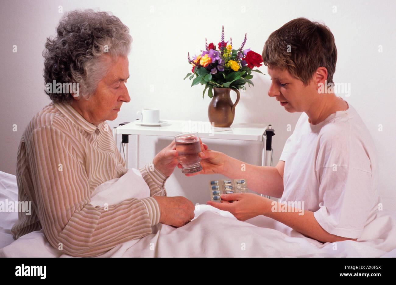 Custode partecipando alla sua anziana cliente Immagini Stock