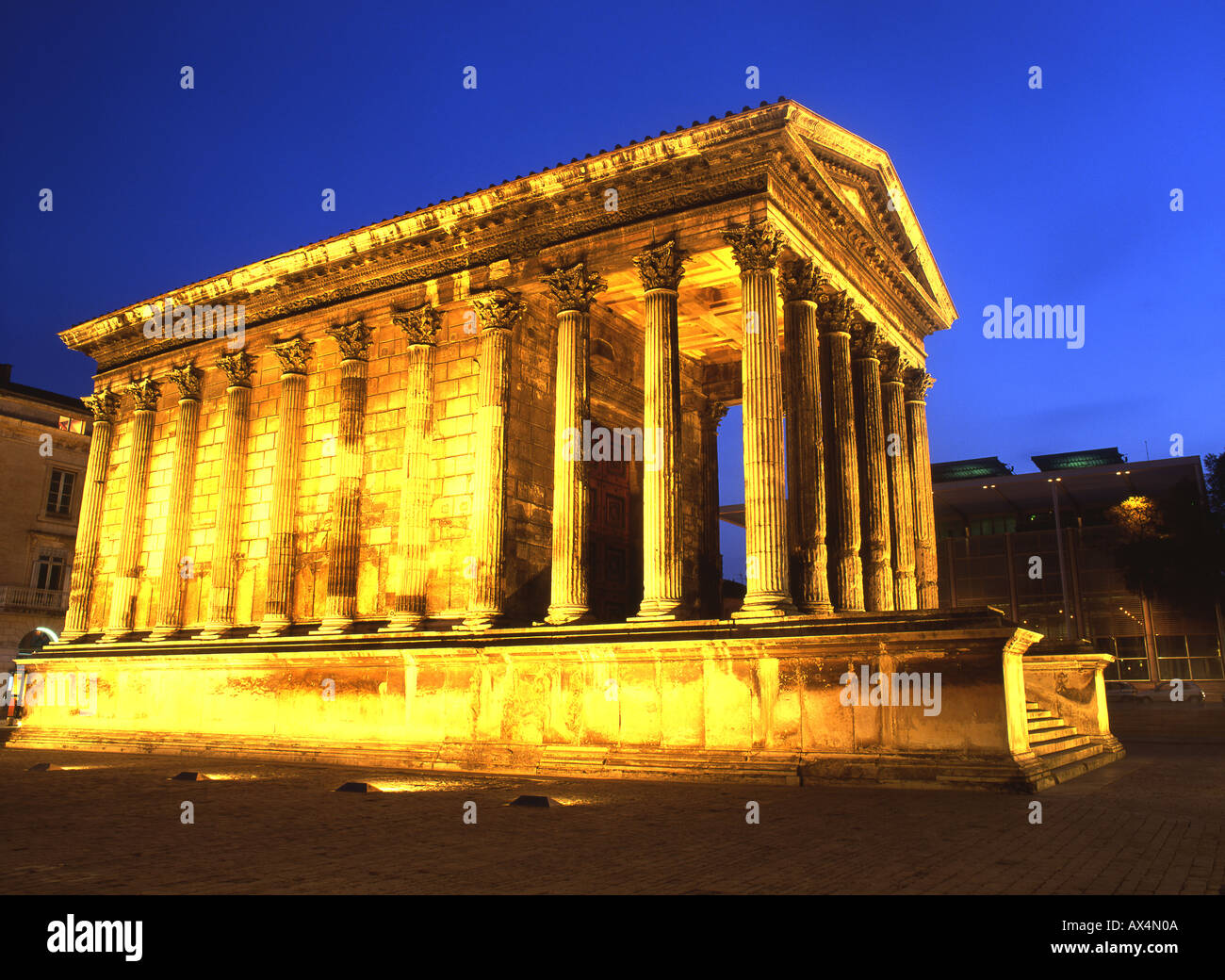 La Maison Carrée II secolo d.c. tempio romano di notte Carrée d'Art Museum di Norman Foster Nimes Languedoc Rousillon & Francia Immagini Stock