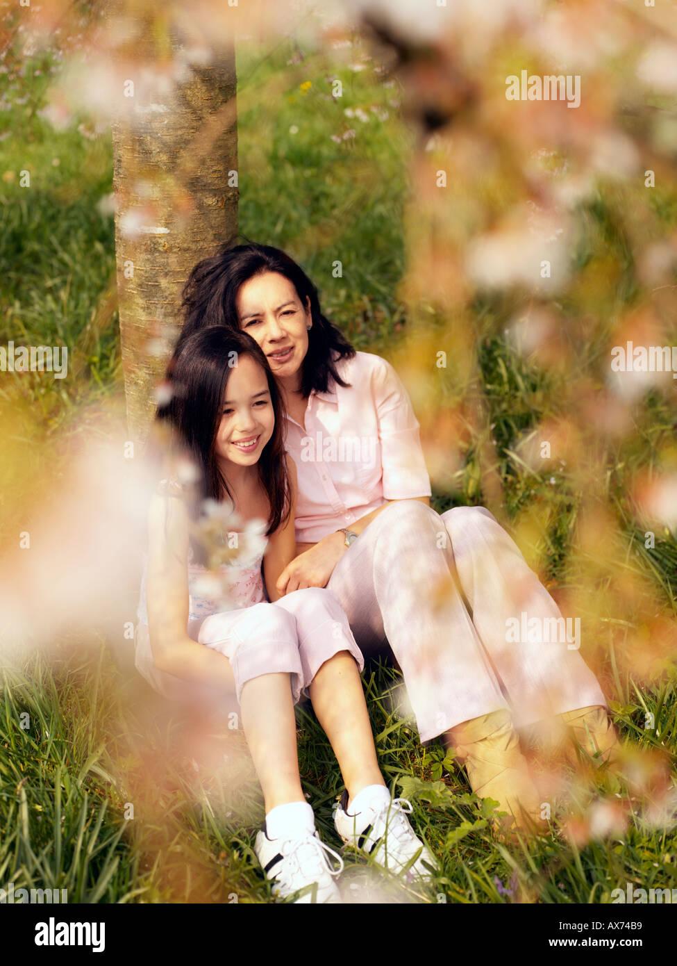 Madre e figlia siede sotto il ciliegio Immagini Stock