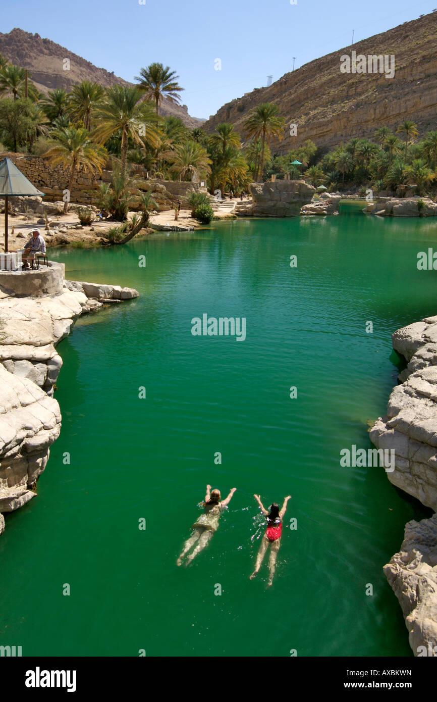 Due ragazze di nuoto nel pool di turchese di Wadi Bani Khalid nella parte orientale delle montagne Hajar del sultanato Immagini Stock