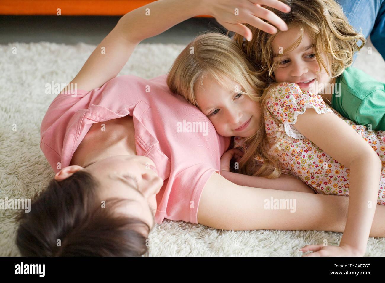 Madre e bambini sdraiato sul pavimento nel soggiorno, ritratto Immagini Stock
