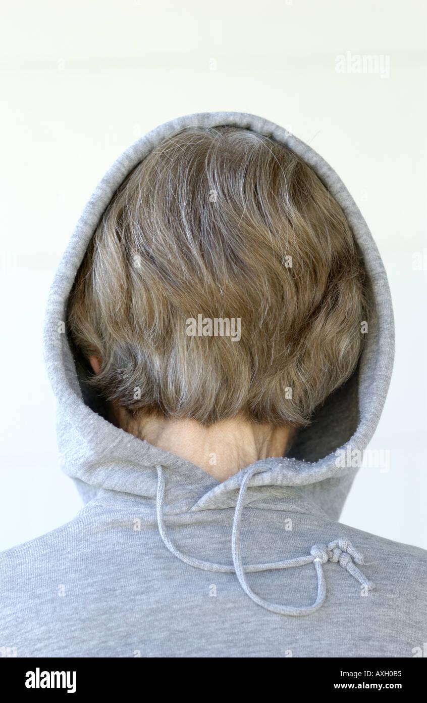 Giovane femmina paziente mentale nascondere indossando un grigio con cappuccio Felpa indietro Immagini Stock