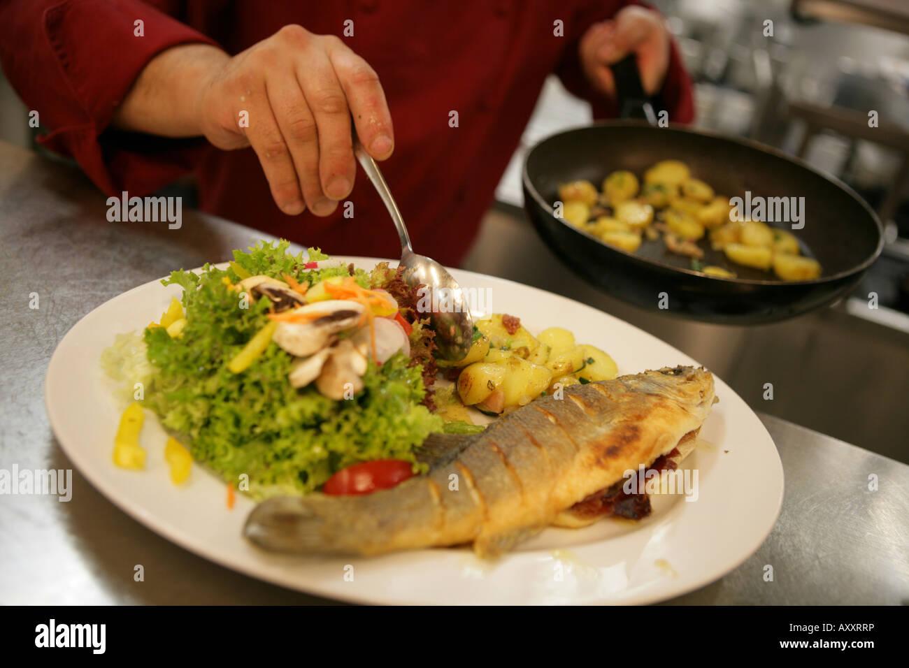 La cucina di un ristorante Decorazione di piastre con un piatto di s ...
