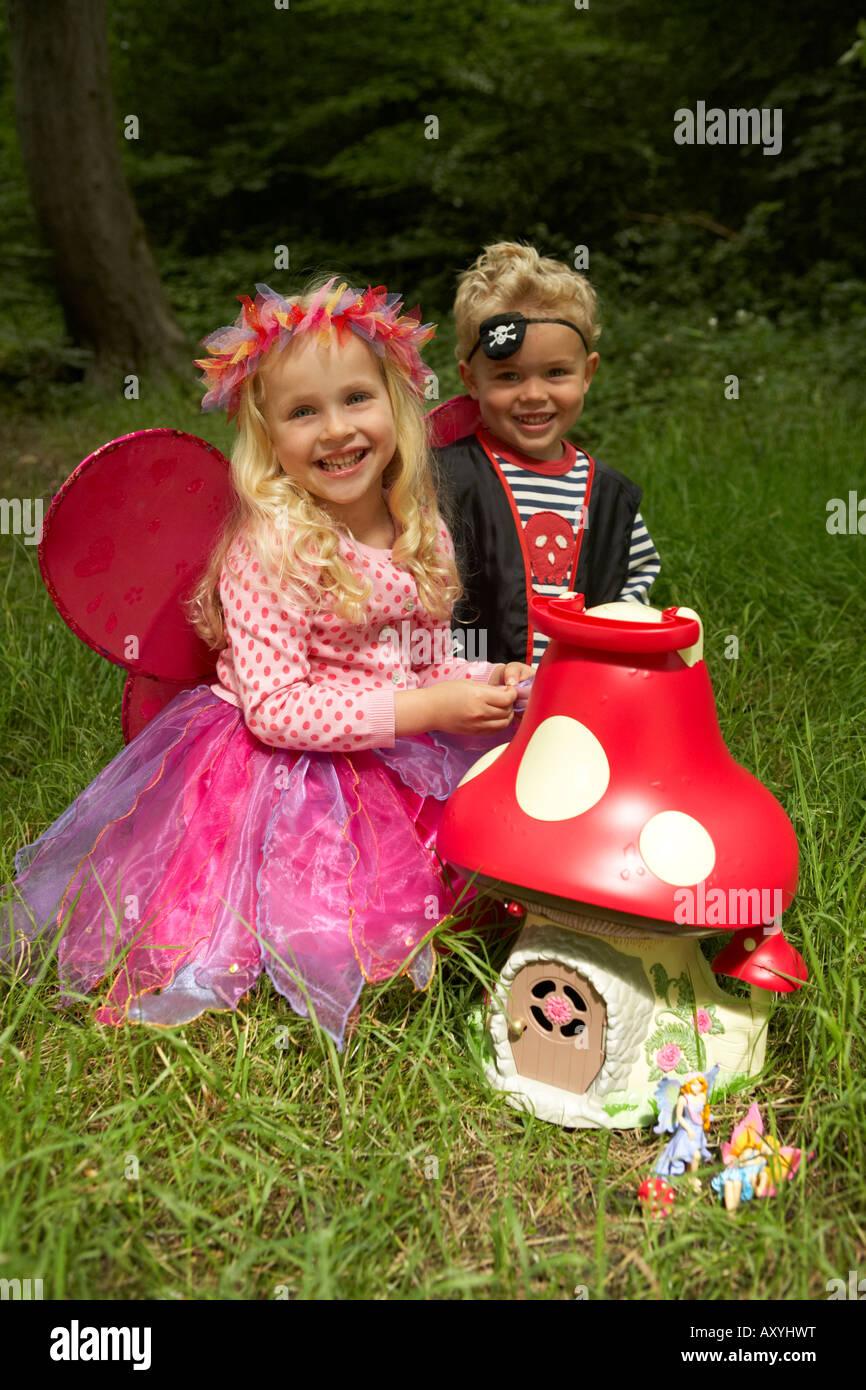 Una ragazza vestita come una fata e un ragazzo vestito come un pirata giocare fuori con una fata toadstool toy Immagini Stock