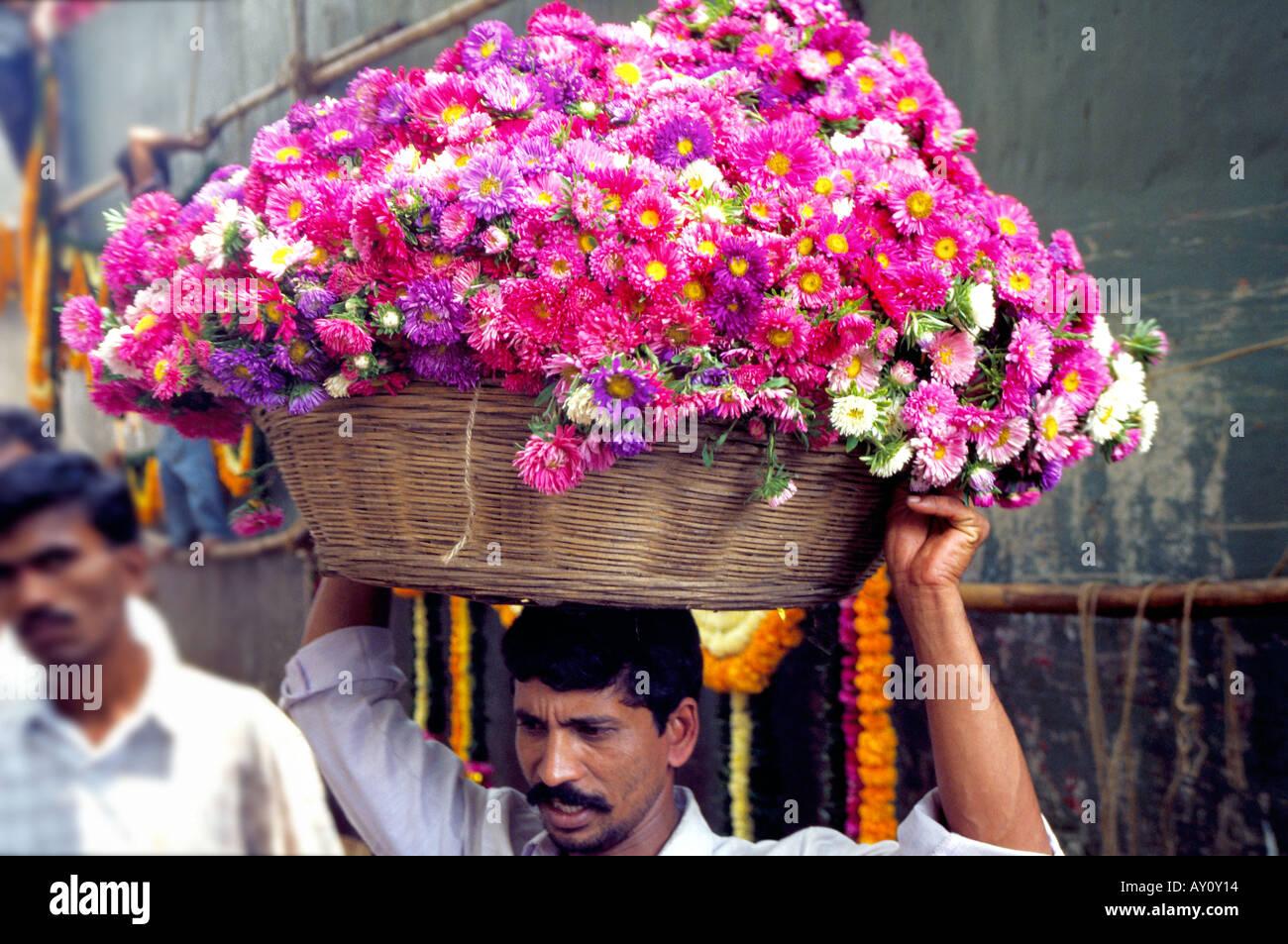 Un facchino che porta un cesto di vimini con un carico di fragrante a Dadar Flower Market il commercio all'ingrosso più grande mercato dei fiori a Mumbai. India Immagini Stock
