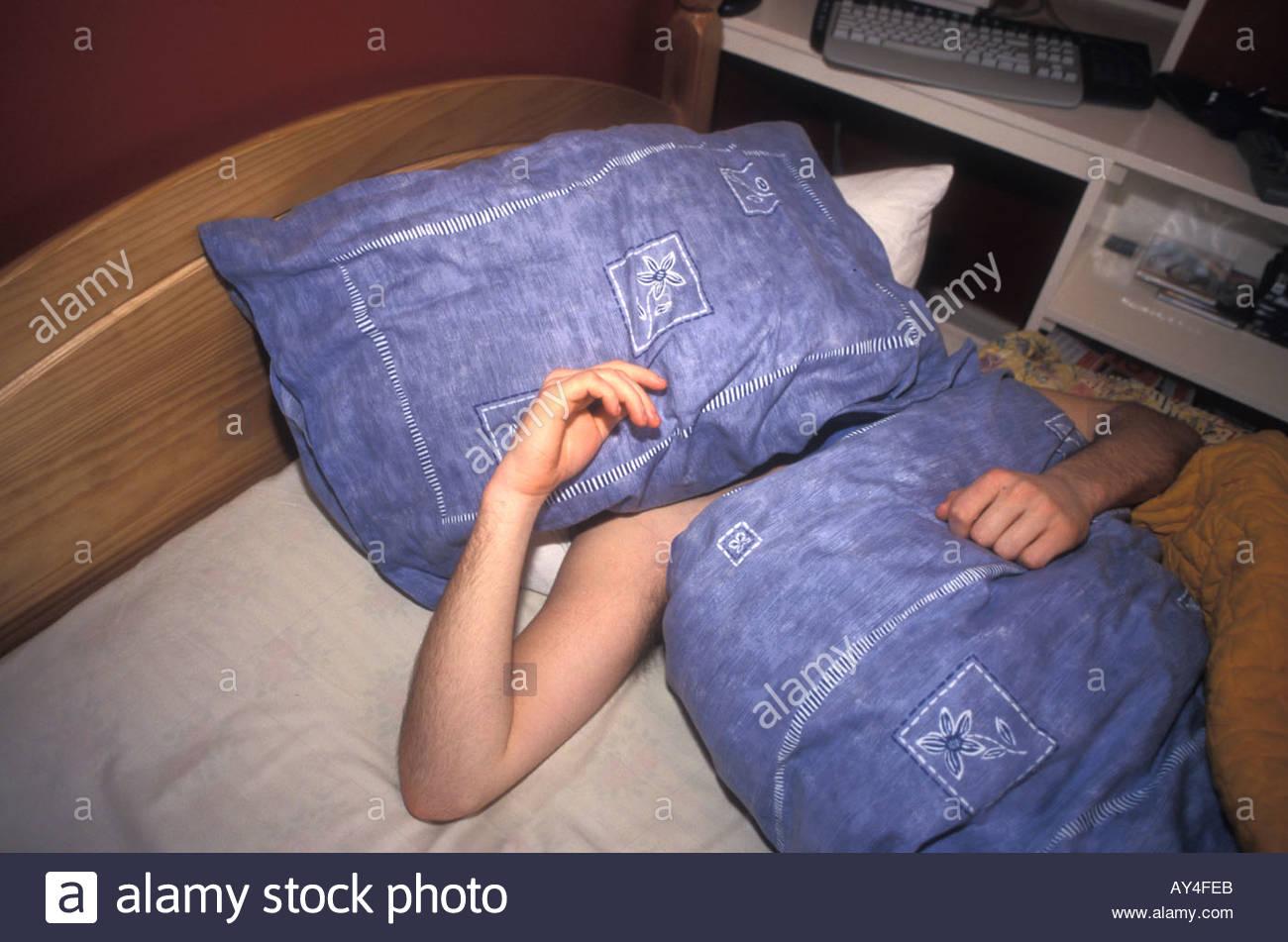 16 anno vecchio ragazzo adolescente addormentato nel letto la mattina non vuole alzarsi REGNO UNITO Immagini Stock