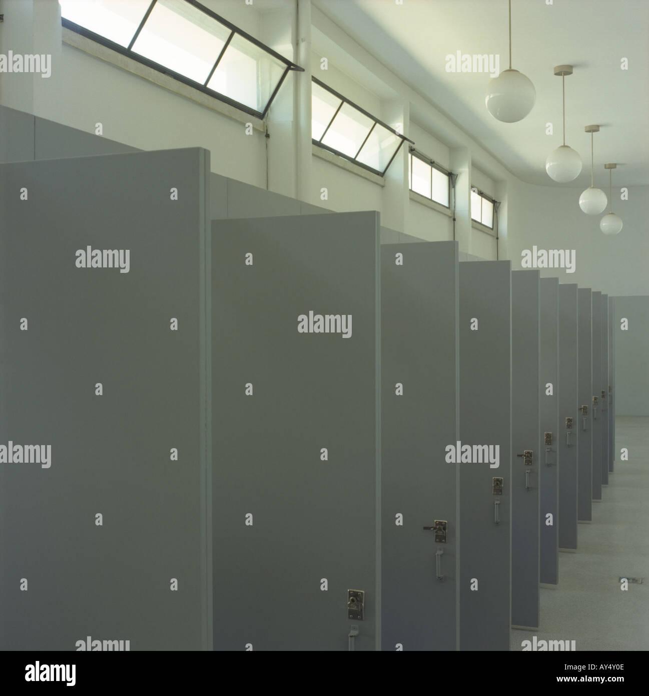 Una lunga serie di porte dei servizi igienici in una scuola Immagini Stock