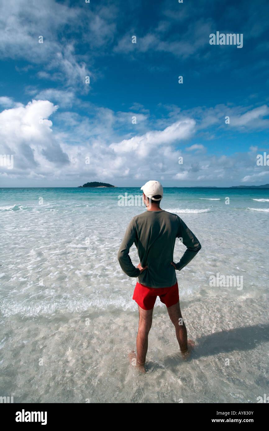 Specchietto del giovane uomo che guarda verso il mare in un giorno chiaro, Whitehaven Beach, isole Whitsundays, Immagini Stock