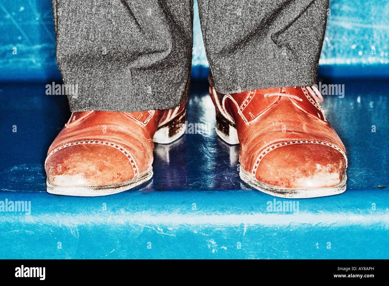 Scarpe di irriconoscibile persona sulle fasi di blu Immagini Stock