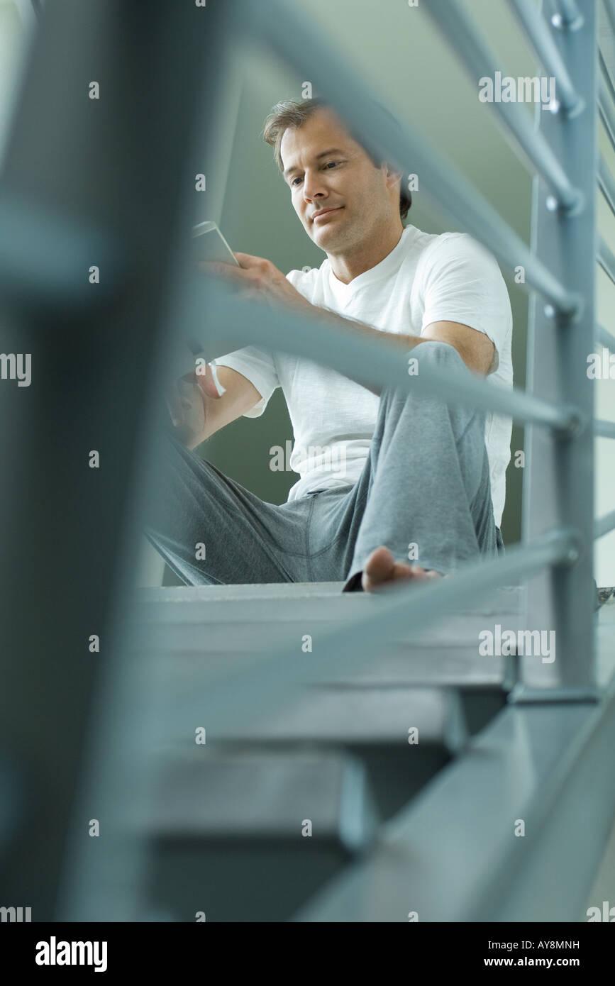 Uomo seduto sulle scale libro di lettura a basso angolo di visione Immagini Stock
