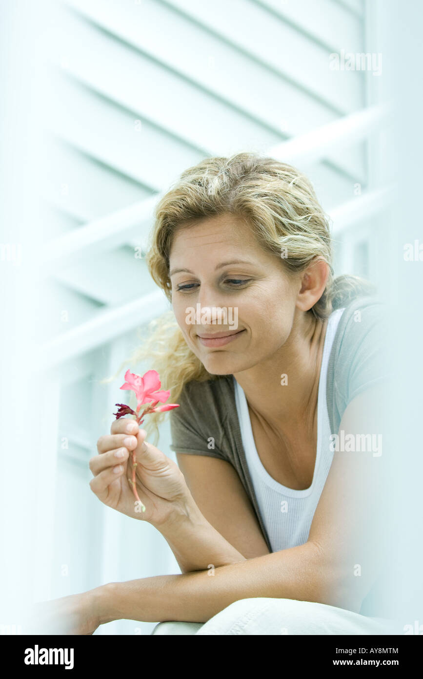 Donna che guarda in basso a fiore in mano, sorridente Immagini Stock