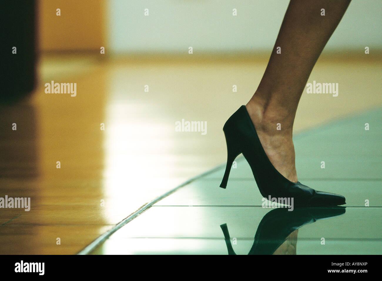 Donna che cammina in tacchi alti, vista ritagliata del piede Immagini Stock