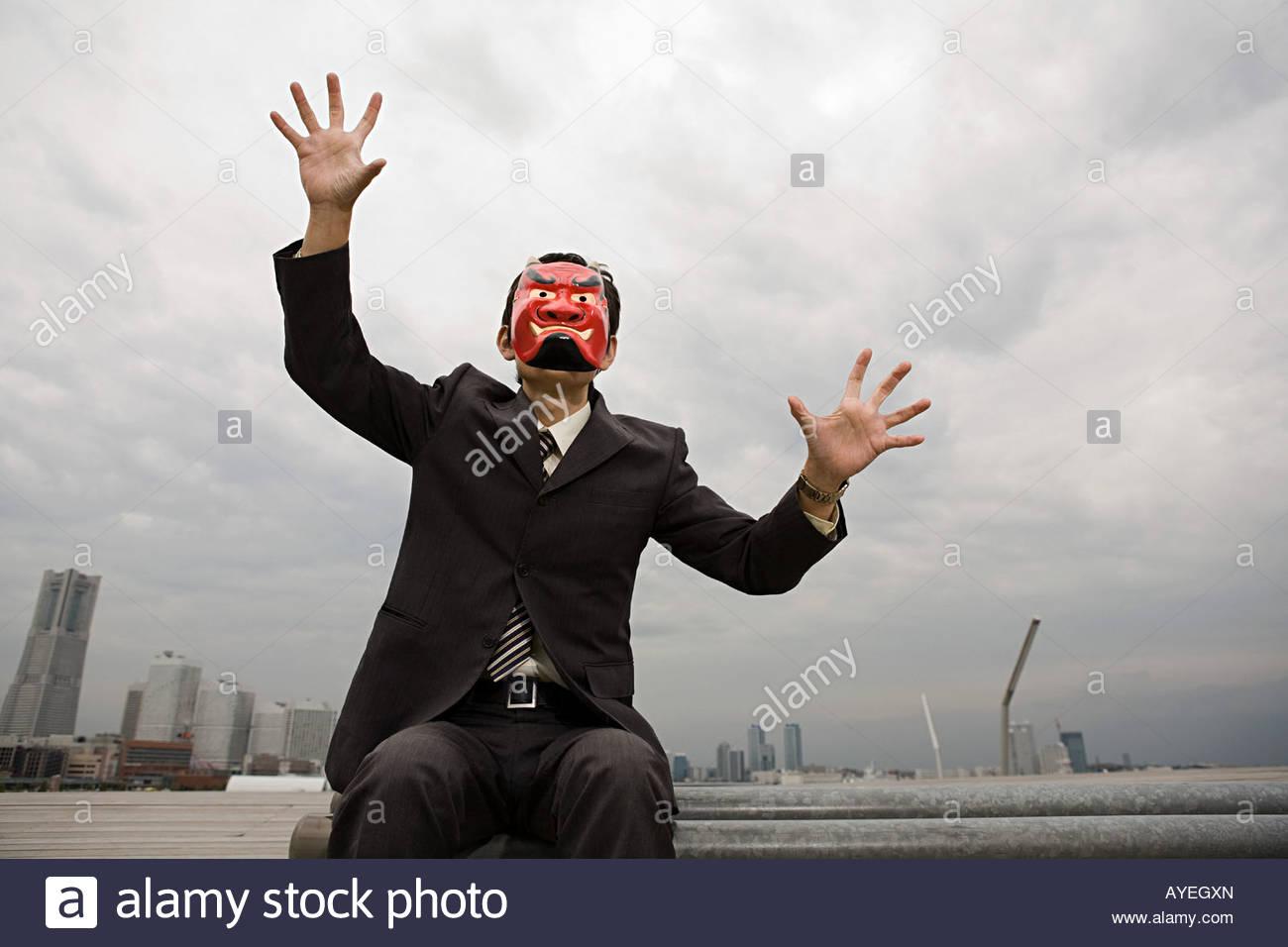 Un imprenditore che indossa una maschera del diavolo Immagini Stock