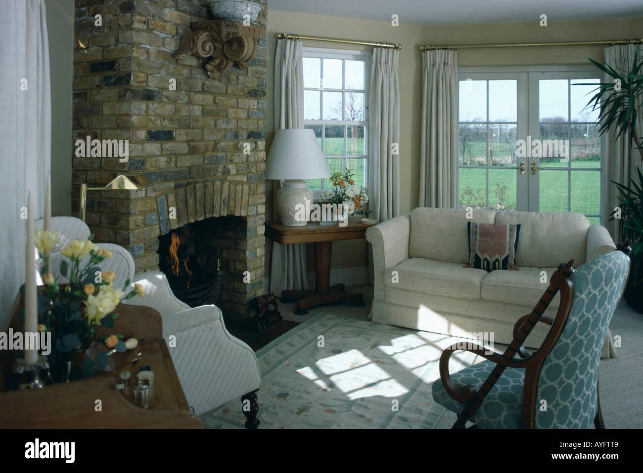 Camino Bianco In Pietra : Divano bianco in cottage stanza vivente con il camino nel muro di