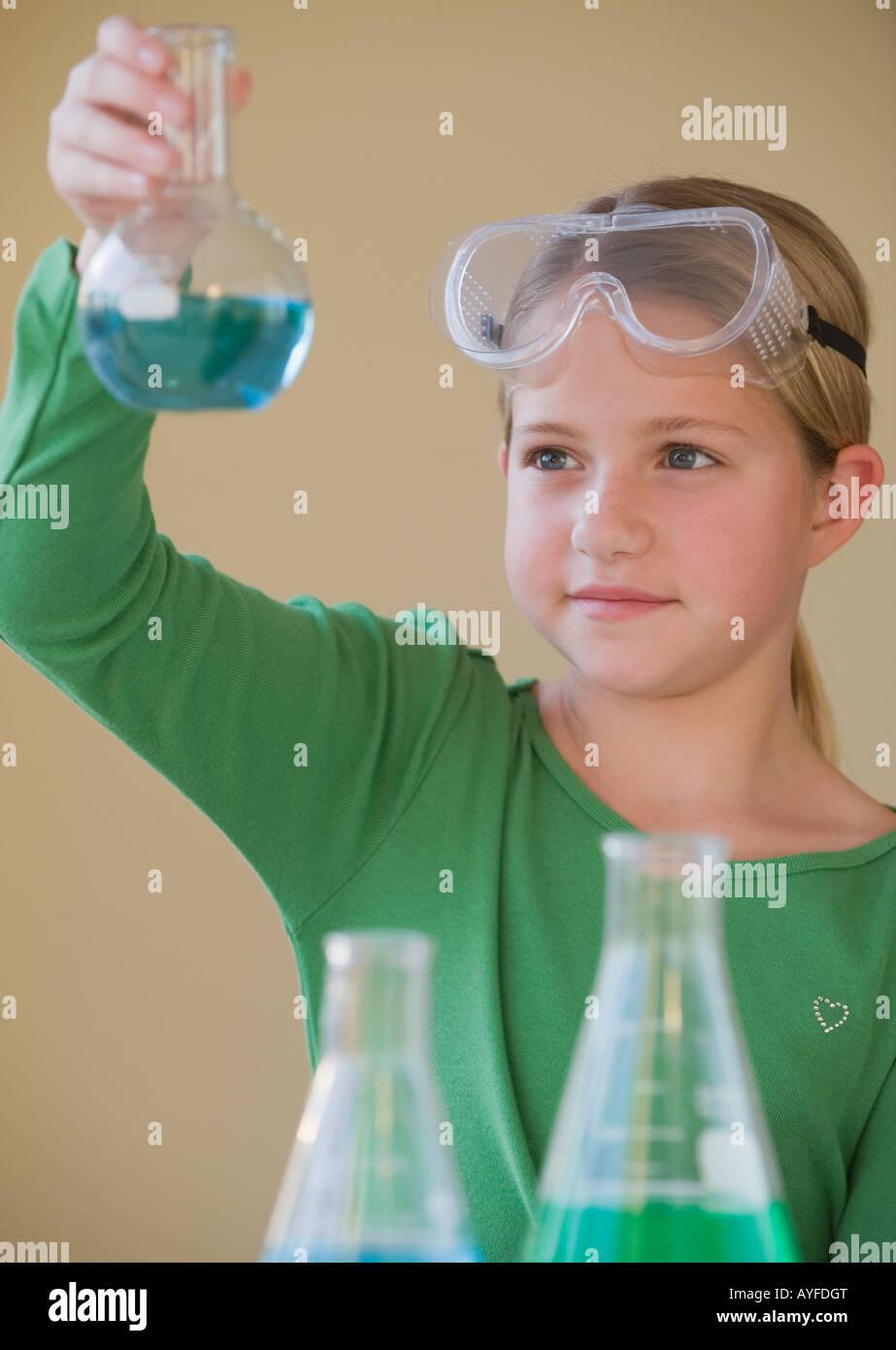 Ragazza nella classe di scienze guardando al bicchiere Immagini Stock