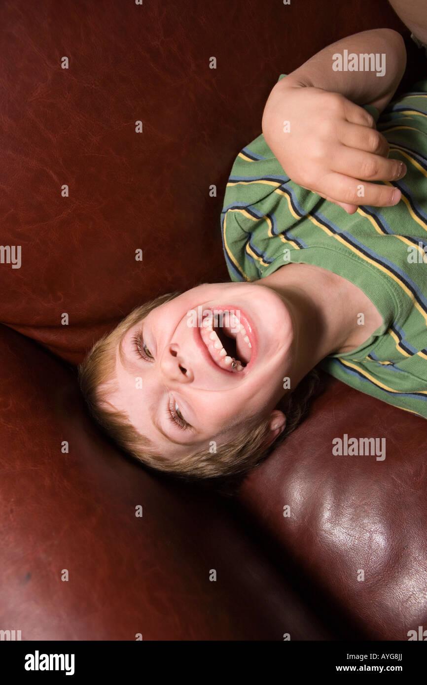 Cinque anni di vecchio ragazzo ridere sul divano di casa Immagini Stock