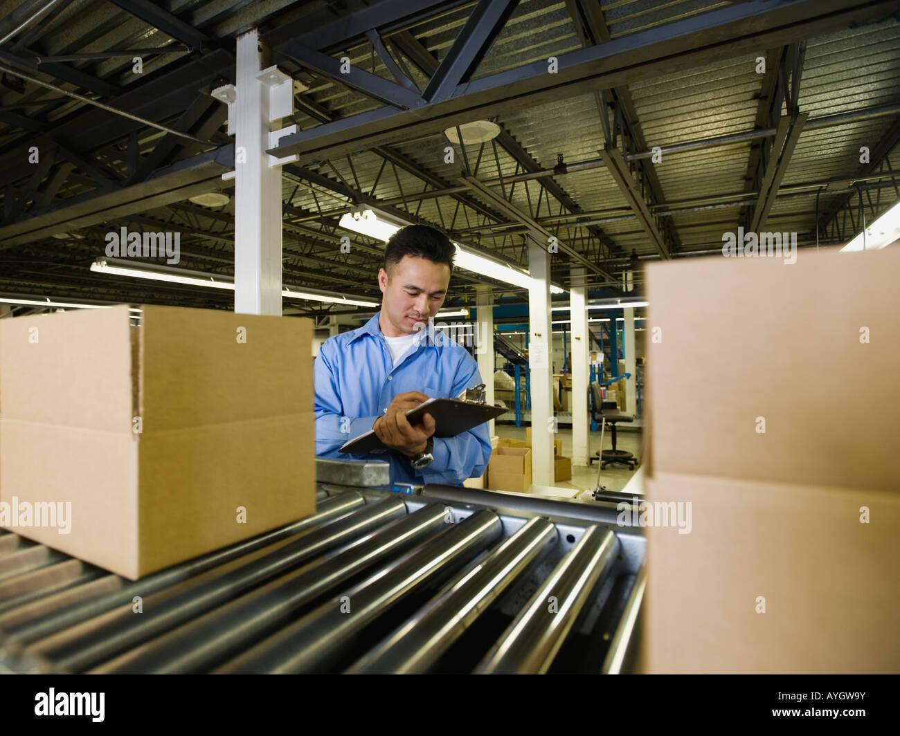 Maschio asiatici operaio di fabbrica prodotto di controllo Immagini Stock