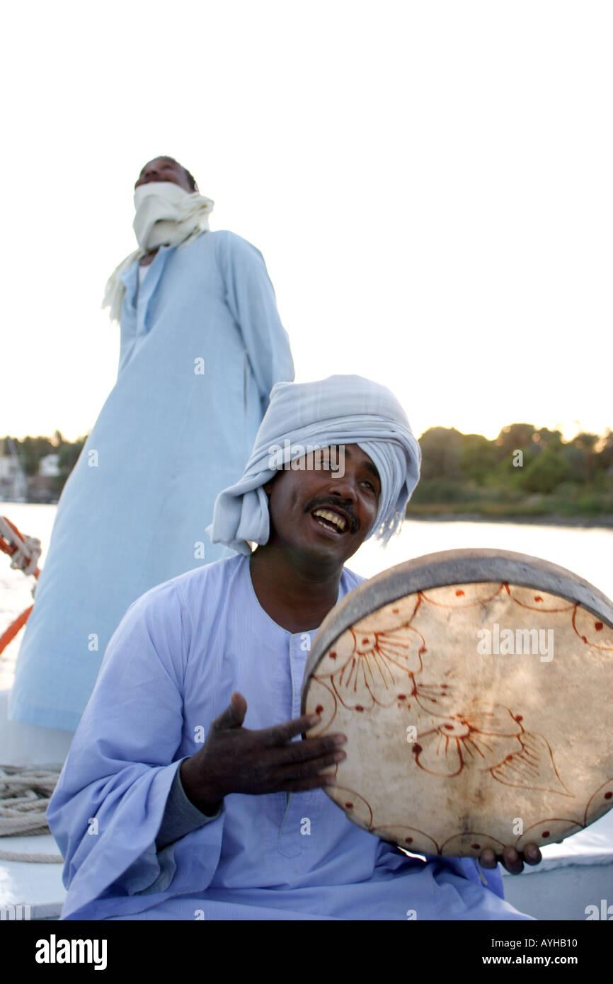Luxor vela il fiume Nilo a bordo di una Feluca sailor in background musicista in primo piano Immagini Stock