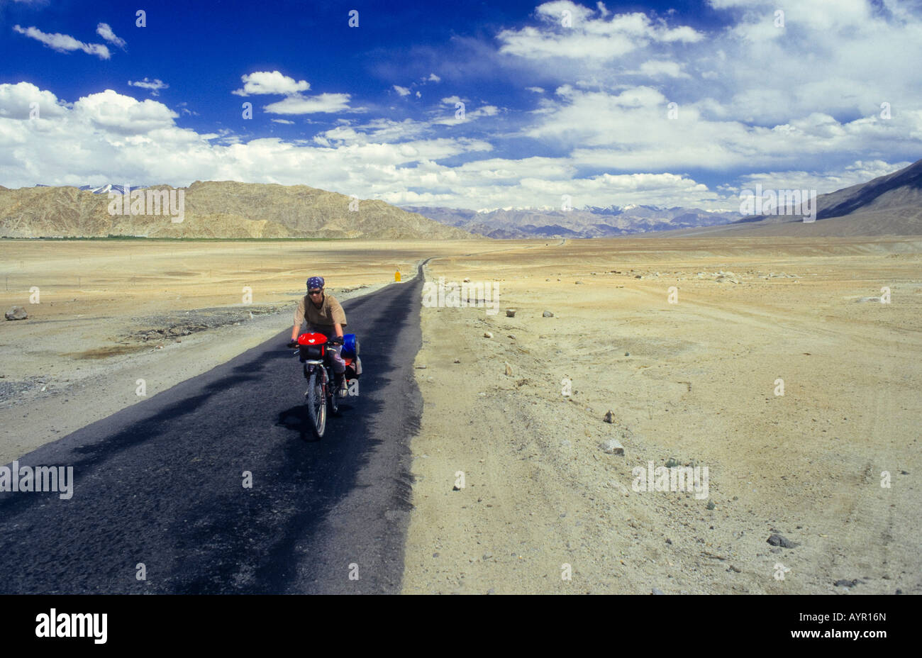 Ciclista indossando la copertura del capo in sella a pieno carico di bici giù un solitario tratto di autostrada Immagini Stock