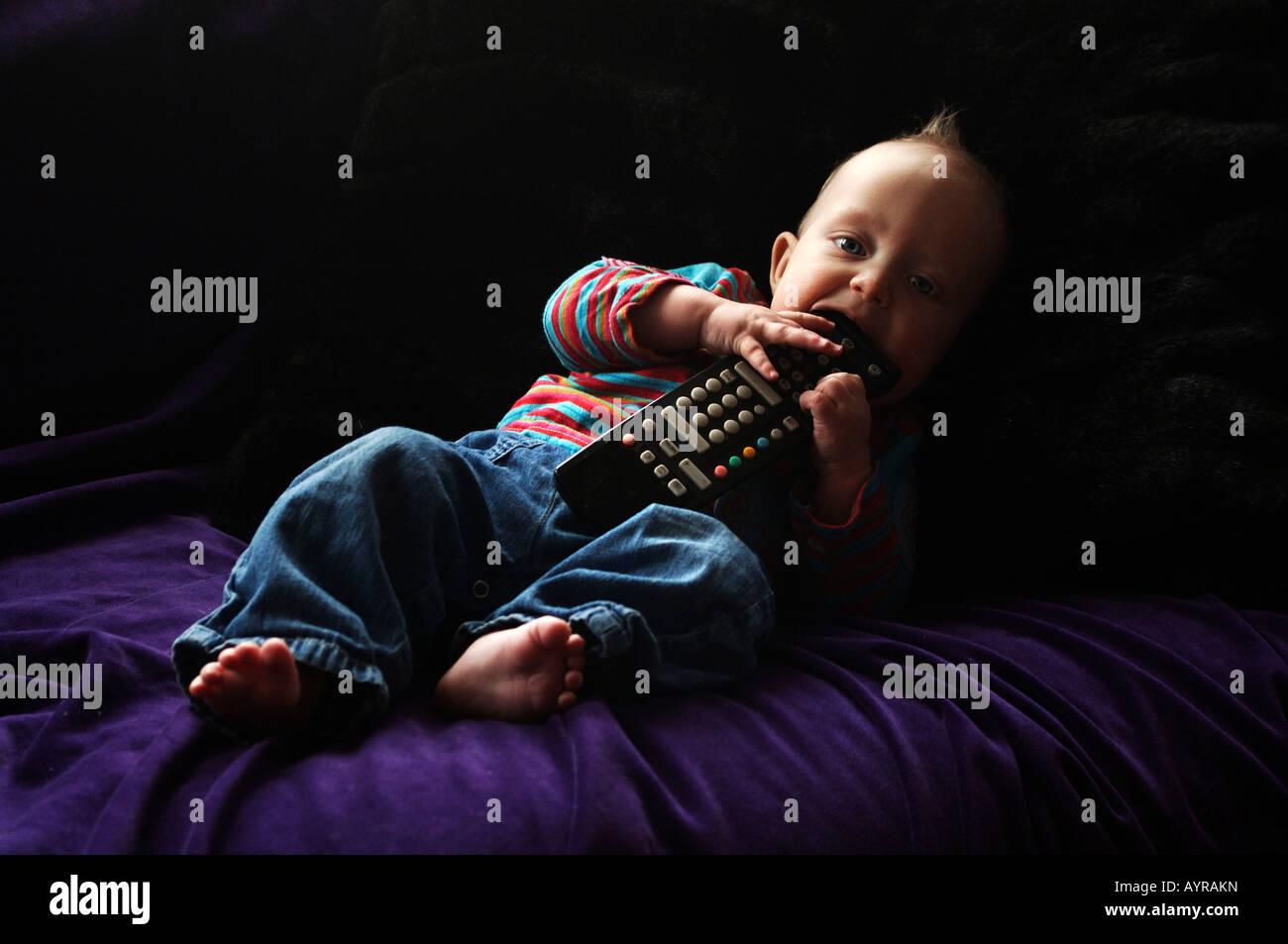 Sei mesi baby boy con il telecomando del lettino Immagini Stock