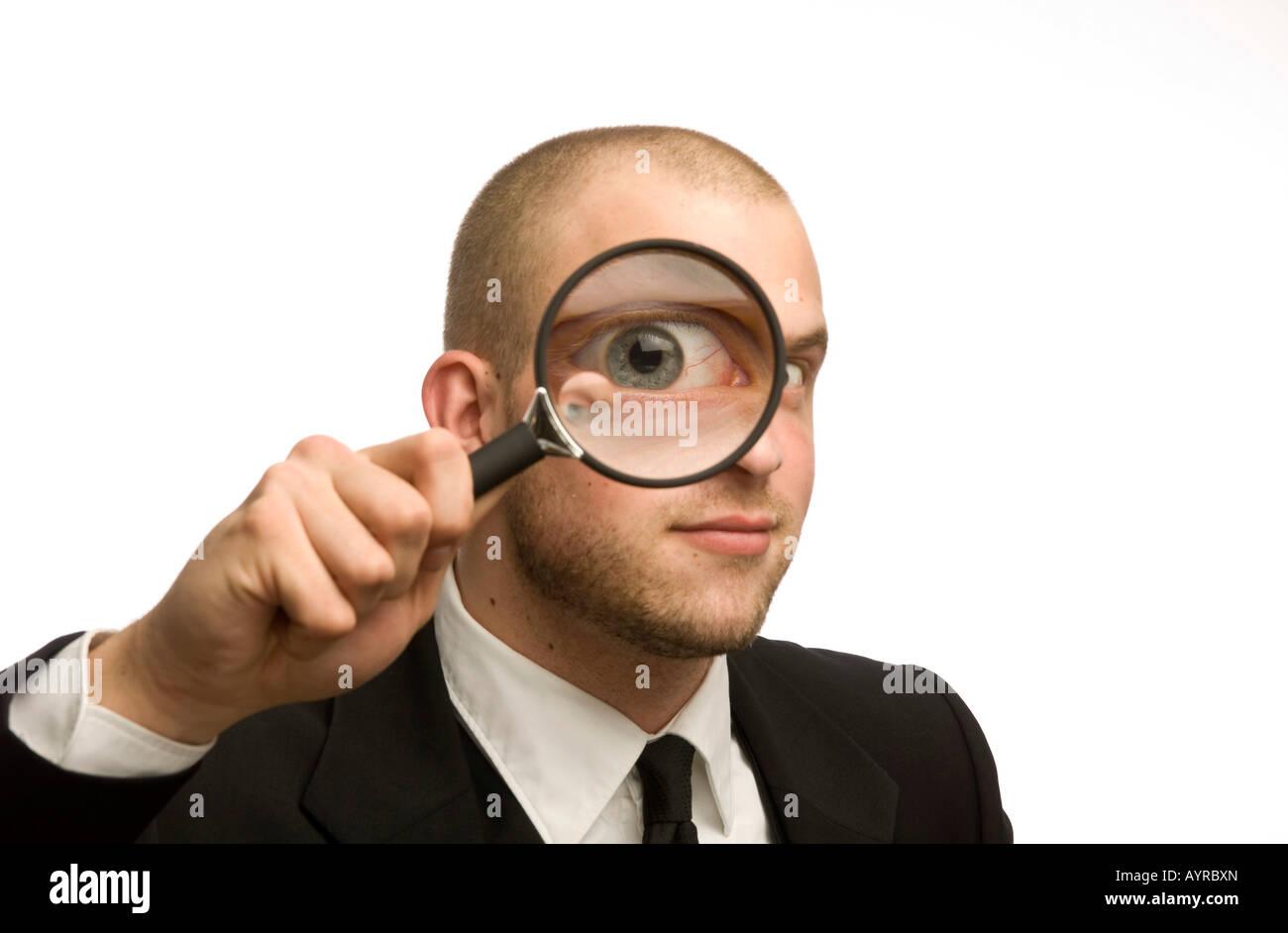 Giovane uomo con lente di ingrandimento nella parte anteriore del suo volto Immagini Stock