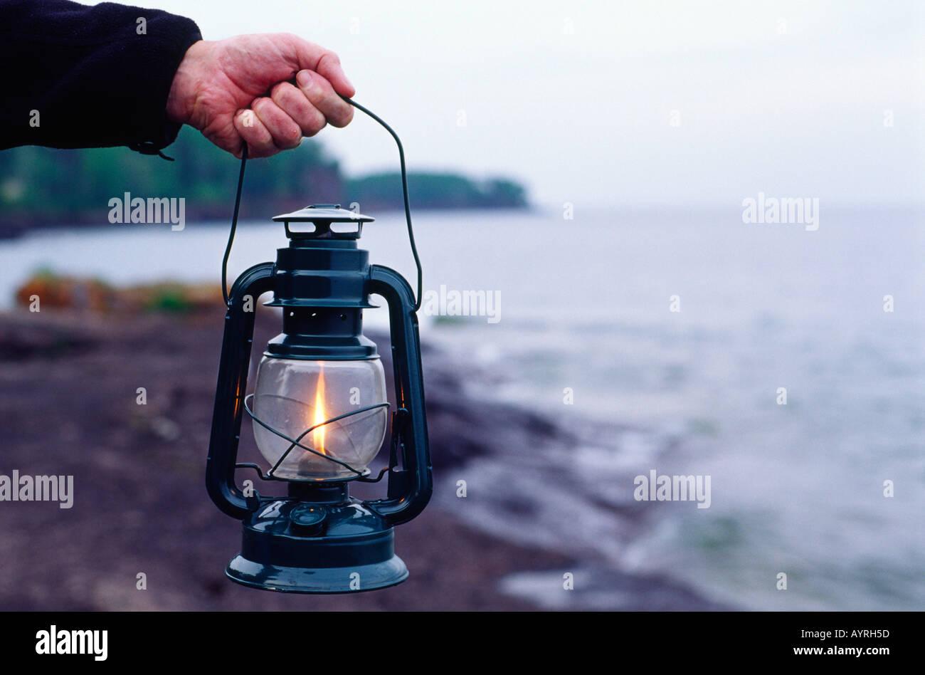 Man mano che trattiene il gas liquido lanterna di carburante sul roccioso riva del lago Superior Minnesota MN USA Immagini Stock