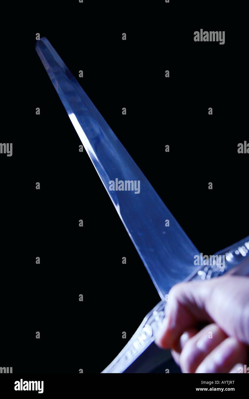 Fantasy splendente spada blu su uno sfondo nero. Immagini Stock