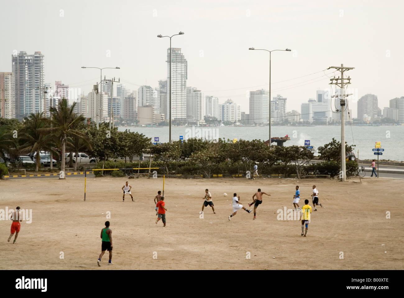 I giovani uomini a giocare il gioco del calcio sul lungomare con Bocagrande dietro a Cartagena de Indias Colombia Immagini Stock