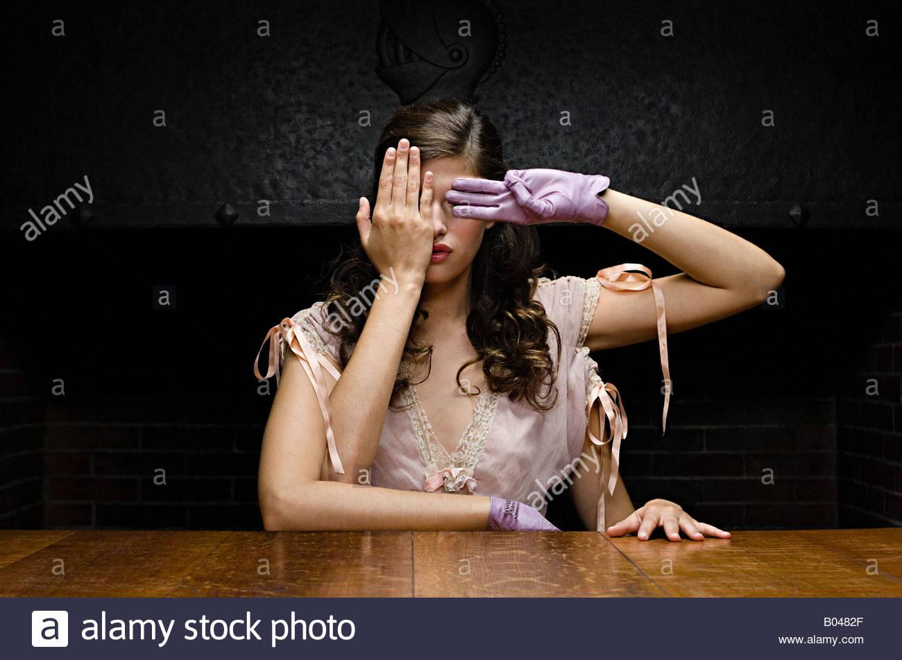 Una donna con quattro bracci che copre i suoi occhi Immagini Stock