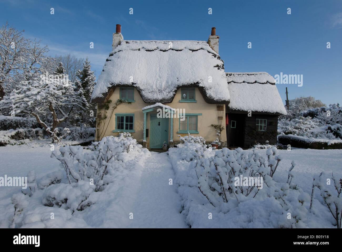 Un cottage con tetto di paglia su una soleggiata giornata nevosa, Warwickshire, Inghilterra, Regno Unito. Foto Stock