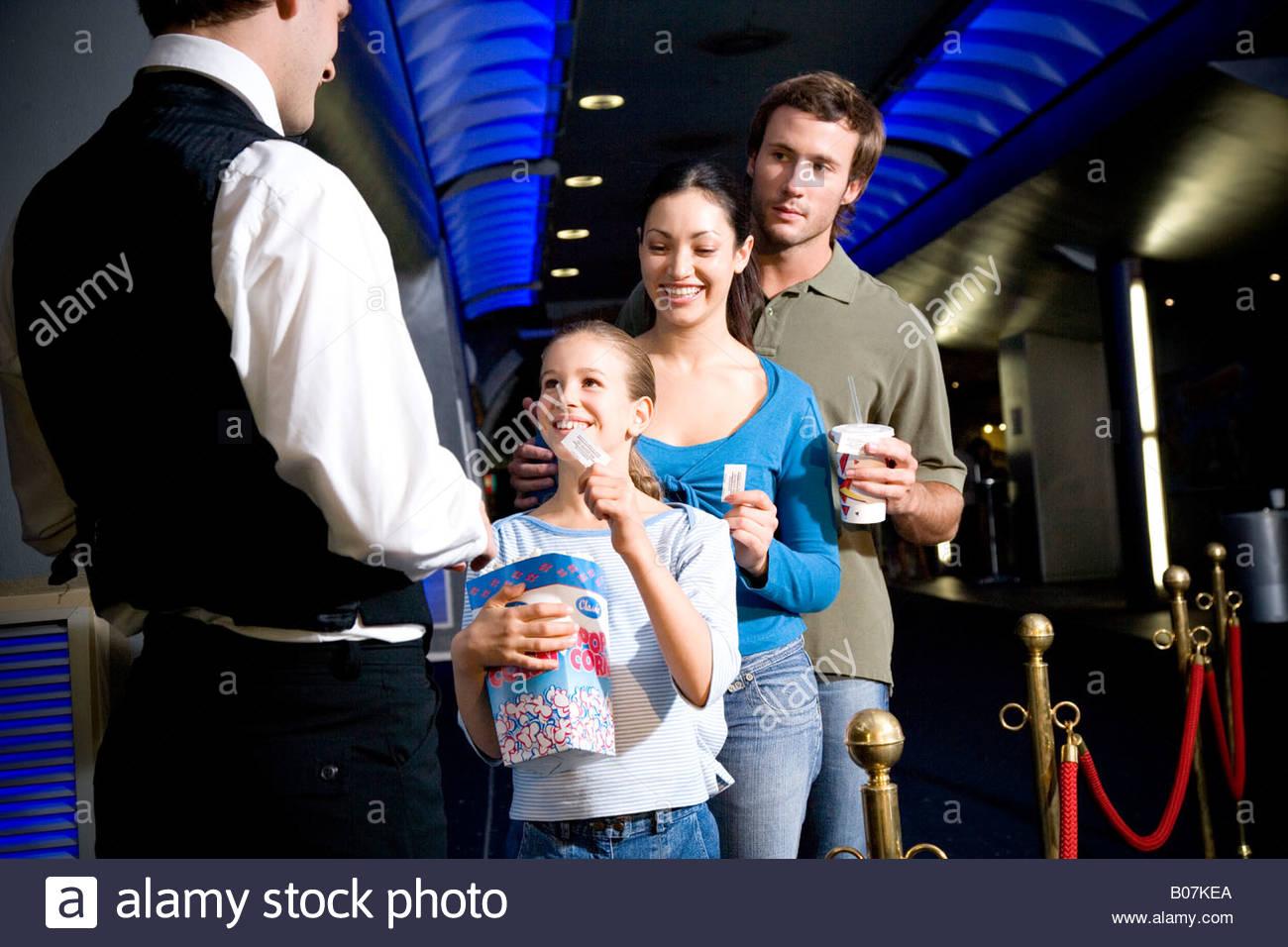 La famiglia presso il cinema di consegnare i biglietti per la usher Immagini Stock