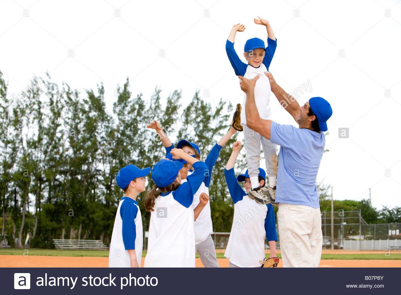 Ragazzo giovane essendo sollevata da little League Baseball coach Immagini Stock