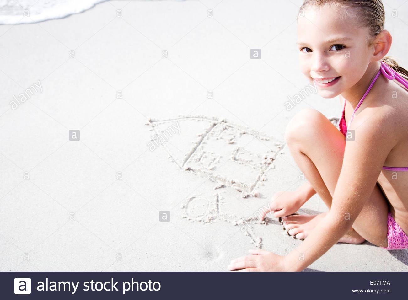 Una giovane ragazza Scritta sulla sabbia Immagini Stock