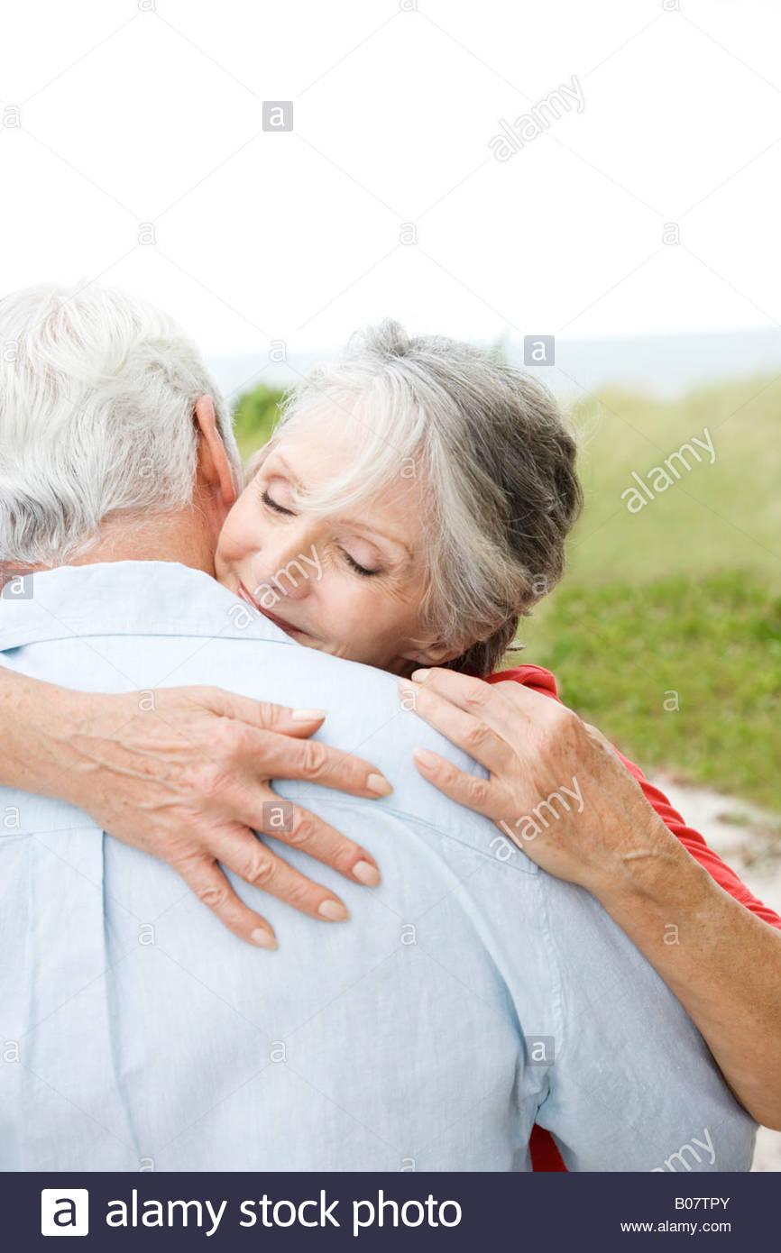 Coppia senior abbracciando in spiaggia Immagini Stock
