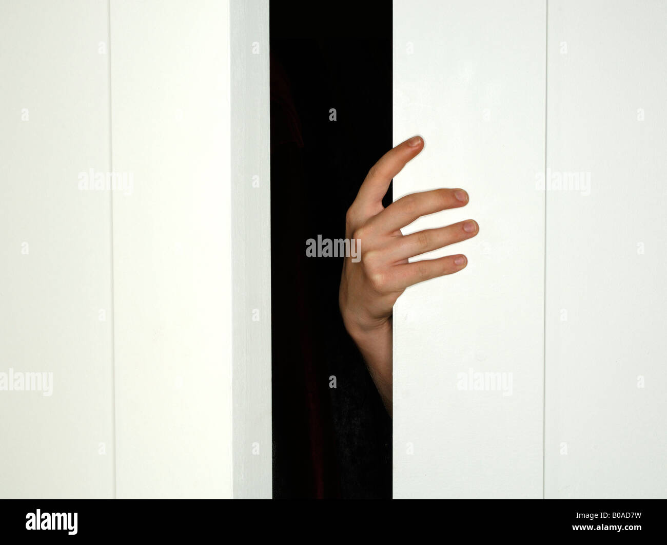 Una mano che tiene aperto chiuso una porta bianca Immagini Stock