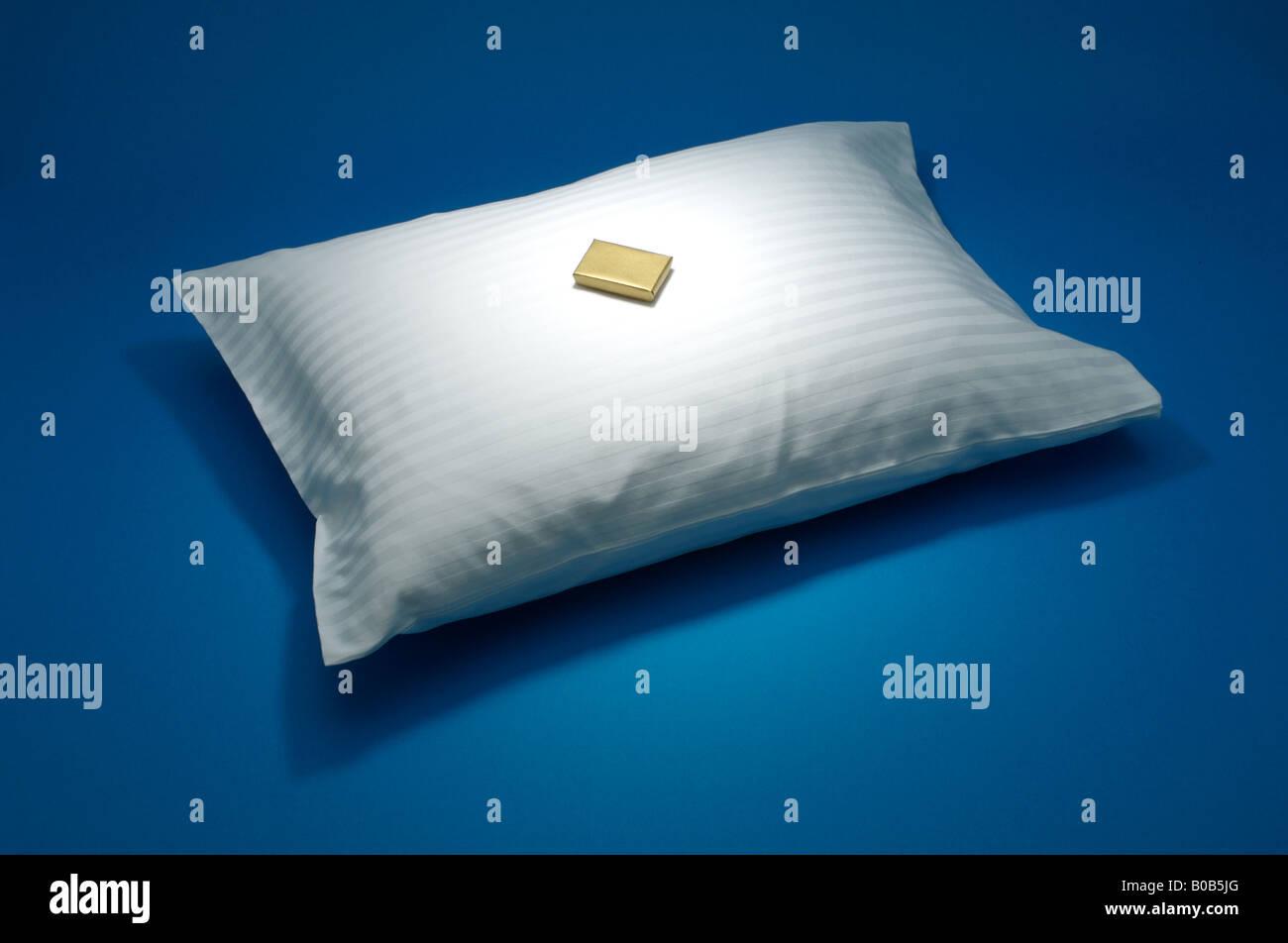 Un cuscino in bianco con una piccola scatola dorata, sfondo blu Immagini Stock