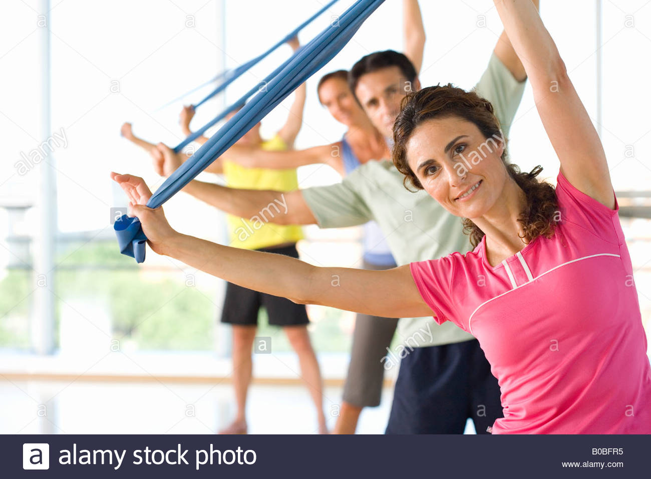 Le persone che la esercitano classe con bande di esercizio, sorridente Immagini Stock