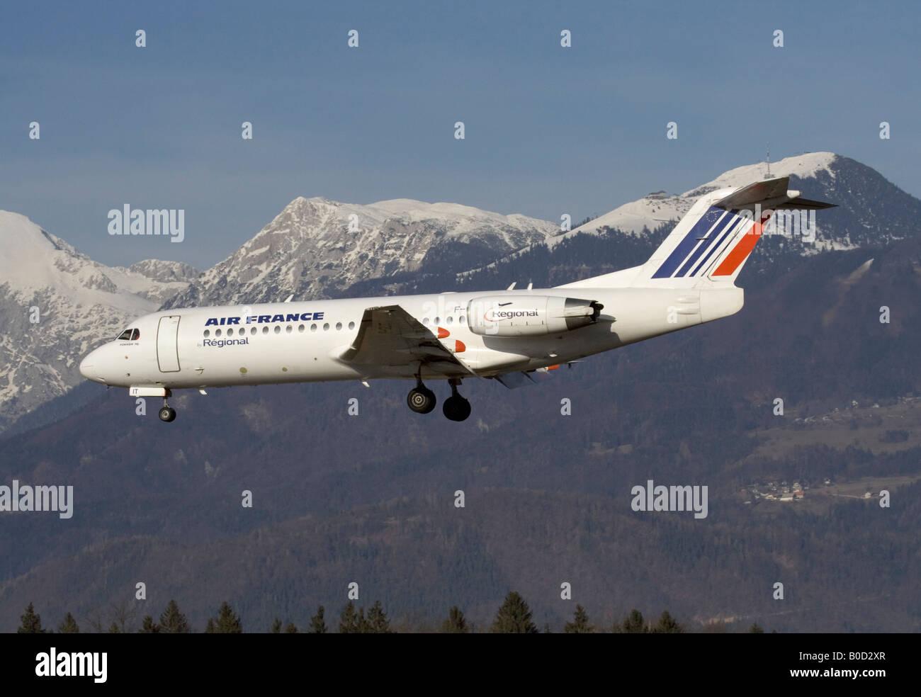 Commerciale viaggi dell'aria. Air France Fokker 70 jet atterraggio aereo con le montagne sullo sfondo, che simboleggiano Immagini Stock