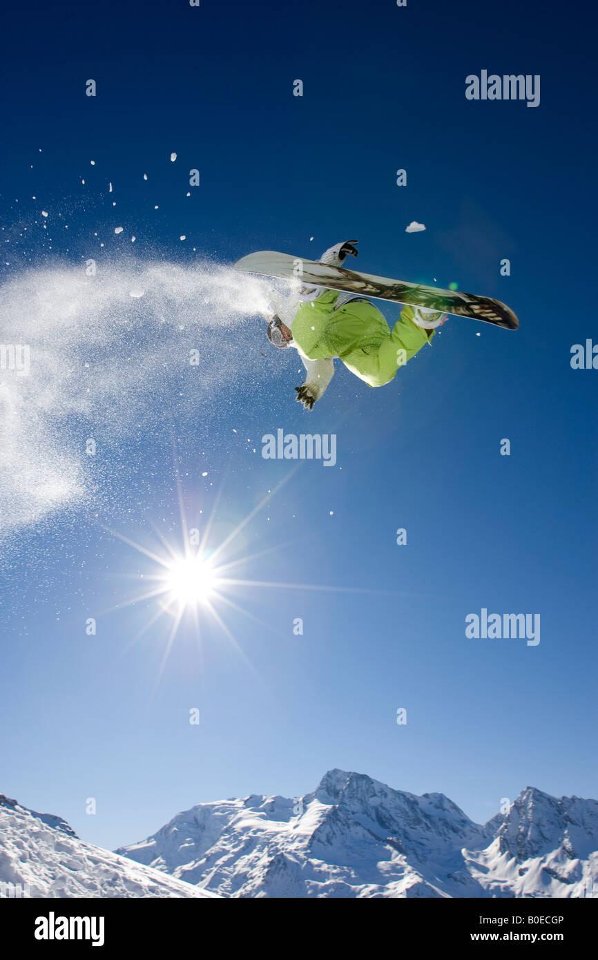 Snowboarder filatura di saltare sulla soleggiata montagna innevata. Immagini Stock
