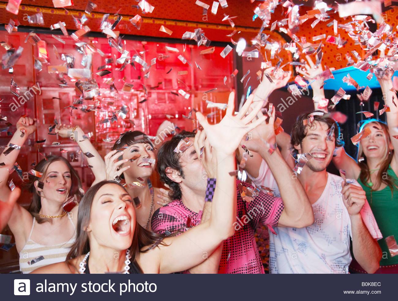 Un gruppo di persone in un night club partying e gettando coriandoli Immagini Stock