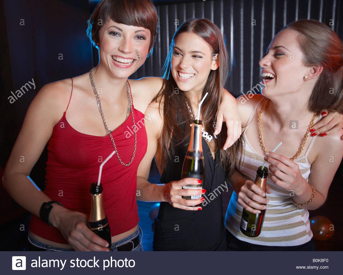Tre donne in un night club di bere e ridere Immagini Stock