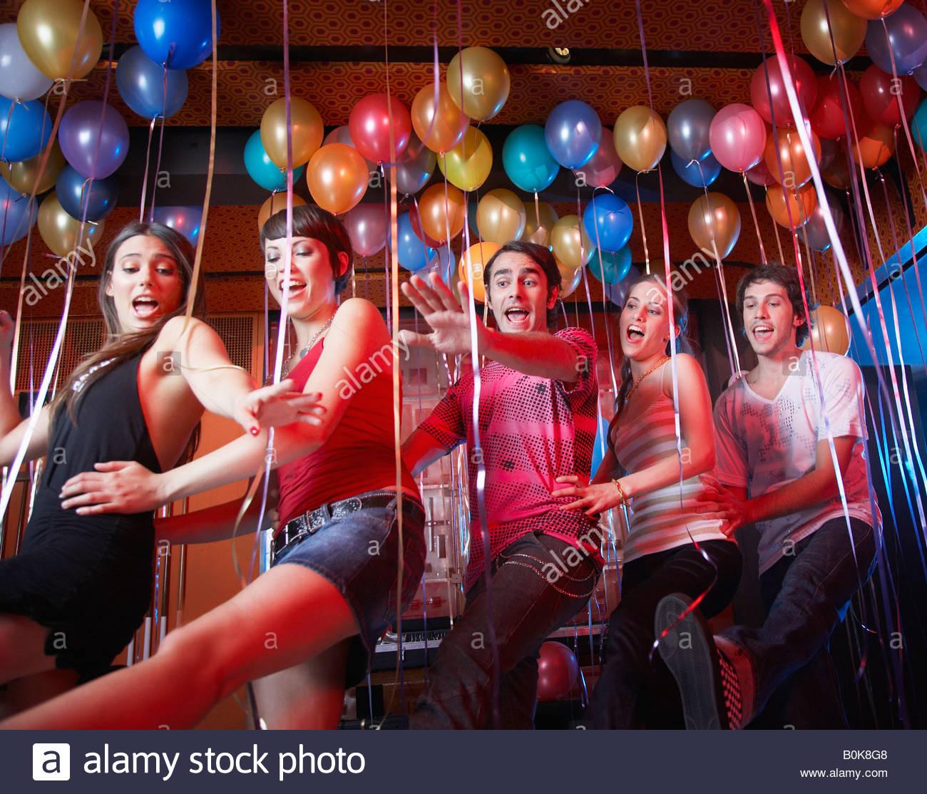 Cinque persone in una discoteca dancing e sorridente Immagini Stock