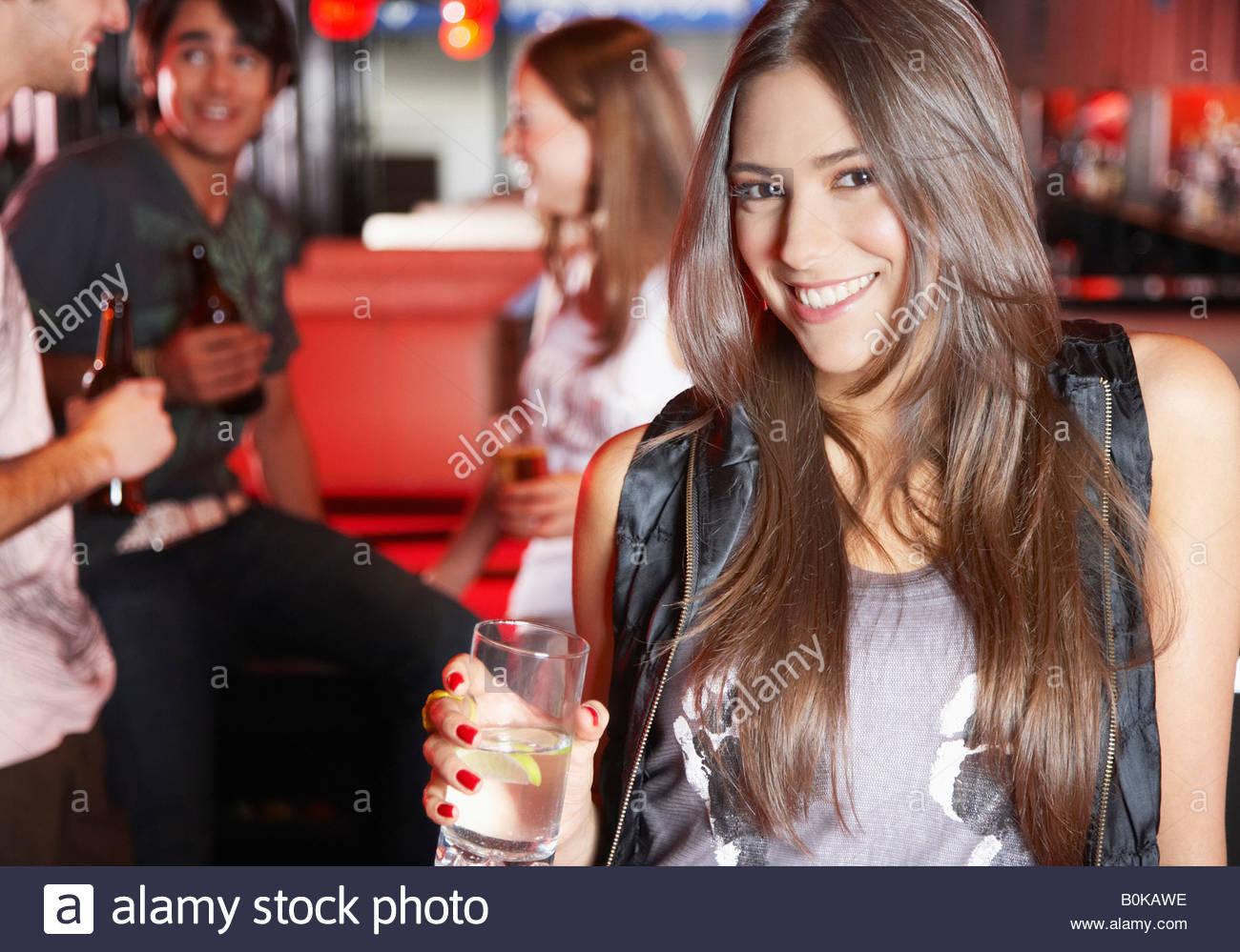 Donna che mantiene la bevanda nel nightclub sorridente Immagini Stock