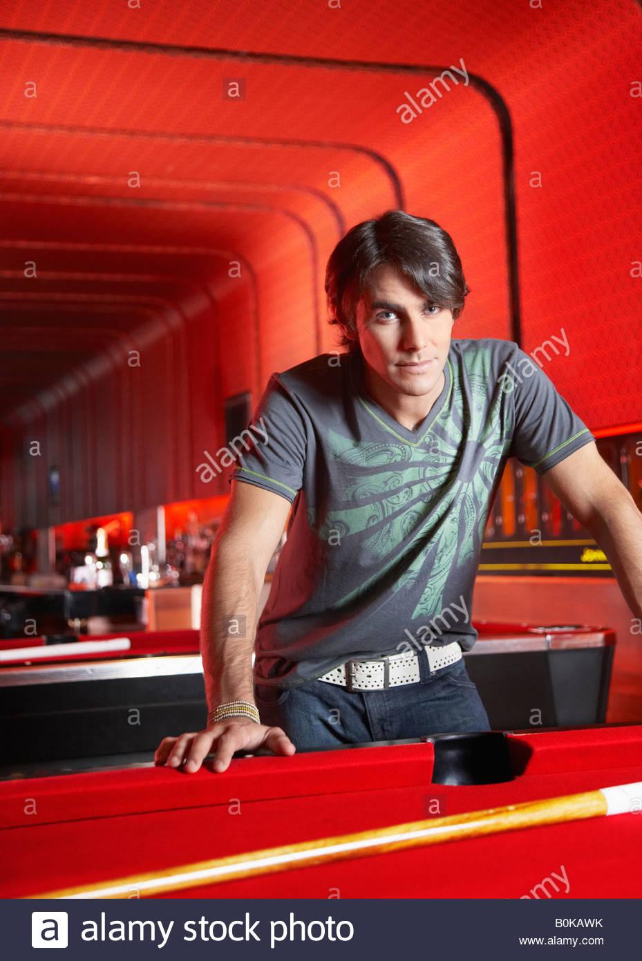 Uomo appoggiato sul tavolo da biliardo Immagini Stock